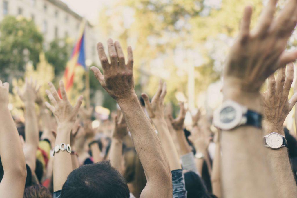 Mixed race group of protestors raising hands.